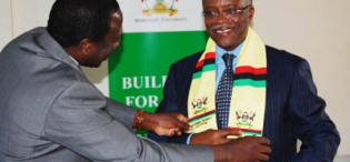 Eng Dr Wana Etyem adorns The Prime Minister with Makerere Alumni Scarf