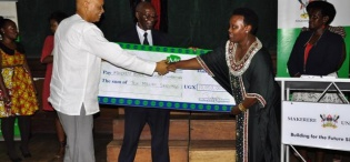 Mrs. Mary Mugyenyi (2nd R) hands over a dummy cheque worth UGX 10m to the Chancellor Prof. George Mondo Kagonyera as Prof. Oswald Ndoleriire-Ag. Principal CHUSS witnesses during the 2nd Joshua Mugyenyi Memorial Lecture, 15th March 2013, Makerere University, Kampala Uganda