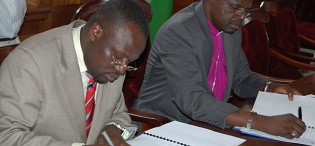 The Ag. Vice Chancellor Prof. V. Baryamureeba (L) and His Grace Henry Luke Orombi sign the MoU between CoU and Makerere University during the His Grace's visit, 24th August 2011, Makerere University, Kampala Uganda