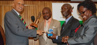 The Chancellor Prof. G.M. Kagonyera hands over an award to Prof. L.S. Luboobi (2nd R), former Vice Chancellor and after 43 years, is CoNAS' longest serving Professor, 20th July 2012, Kampala Serena Hotel, Uganda