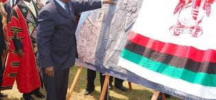 H.E. President Mwai Kibaki of Kenya (R) gets a feel of the artwork of the plaque symbolizing the Launch of Constituent Colleges on 24th January 2012, Makerere University, Kampala Uganda