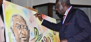 H.E. John Kufuor (L) autographs the souvenir live painting after delivering a Public Lecture on Oil, Mak@90, 2nd August 2013 Makerere University, Kampala Uganda