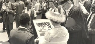 Her Majesty Queen Elizabeth, the Queen Mother and Principal Sir Bernard de Bunsen admire a framed portrait of the College at Makerere University, Kampala Uganda on 20th February 1959