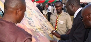 Mr. Mutekanga Igaga signs the Mak@90 Grand Finale commemorative live painting on 3rd August 2013 at the Freedom Square, Makerere University, Kampala Uganda. 3rd Right is the artist Rolands Tibirusya.