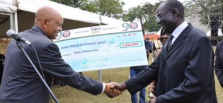 Mr. Grace Wilson Mutekanga Igaga, The Makerere Anthem composer receives his recognition cheque from the Chancellor Prof. Mondo Kagonyera (L) during the Mak@90 Grand Finale Celebrations, 3rd August 2013, Freedom Square, Makerere University, Kampala Uganda