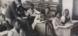 Prof. Josephine Nambooze (2nd R) attends a Science Class as the lecturer (standing) assists a student with his work in the 1950s, Makerere University, Kampala Uganda