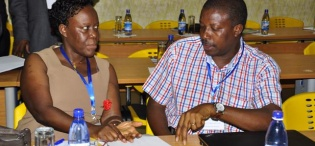 L-R: DVCAA Prof. Lillian Tibatemwa-Ekirikubinza and CAES Deputy Principal Prof. Frank Kansiime confer during the NORHED Programme launch, Hotel Africana 6th March 2013