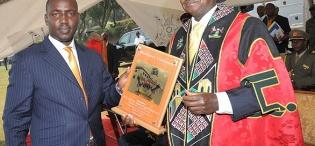 H.E. President Yoweri Kaguta Museveni displays the award received from the Chairman Makerere Convocation, Bruce Kabasa during H.E. Mwai Kibaki's Honorary Doctorate of  Laws Award ceremony, 24th January 2012, Makerere University, Kampala Uganda