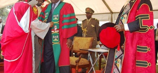 Kenyan President H.E. President Mwai Kibaki is adorned with the PhD gown and Cap by Prof. Grace K. Batebya and Ag. Vice Chancellor Prof. Venansius Baryamureeba during his Honorary Doctorate of  Laws Award ceremony, 24th January 2012, Makerere University, Kampala Uganda