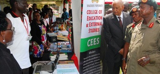 Mr. Titus Okumu, E-Learning Manager explains the platform's importance to President Museveni as he visited the College of Education and External Studies (CEES) stall during his tour of the exhibition on 4th August 2012, Makerere University, Kampala Uganda