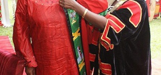 Ms. Rehema Kawawa is assisted into the PhD gown by the Deputy Vice Chancellor (Academic Affairs) Prof. Lillian Tibatemwa-Ekirikubinza during the Honorary Doctorate of Law Award Ceremony on 12th December 2010, Makerere University, Kampala Uganda