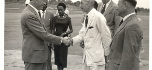 Sir Fredrick Crawford, K.C.M.G, O.B.E,  on arrival at Entebbe Airport on 26th February 1957, shaking hands with Mr. C.H. Bird, Minister of Commerce and Works. To  the right of Mr. Bird are C.H. Haetwell, Chief Secretary, and Mr. R.L.E. Dreshfield, Attorney-General. Also in the picture are Mr. A.K. Kironde,  Asst. Minister of Social Services, and Mrs. Kironde.