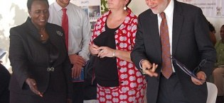 Dr. Jane Bosa (L) ushers U.S. Ambassador Scott DeLIsi to his seat during the SMC Launch on 11th December 2012, Makerere University Hospital, Kampala Uganda