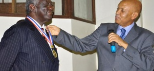 H.E. John Kufuor (L) receives the Convocation Medal from the Chancellor Prof. George M. Kagonyera after delivering a Public Lecture on Oil, 2nd August 2013 Makerere University, Kampala Uganda