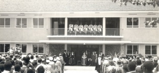 Her Majesty Queen Elizabeth, the Queen Mother then Chancellor University of London, Staff and Studens stand as the National Anthem is played by the Police Band at Makerere Univeristy, Kampala Uganda, 20th February 1959