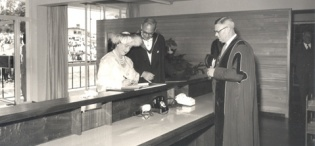Her Majesty Queen Elizabeth, the Queen Mother assisted by the Principal Sir Bernard de Bunsen signs the visitors' book in the New Library Building at Makerere University, Kampala Uganda on 20th February 1959