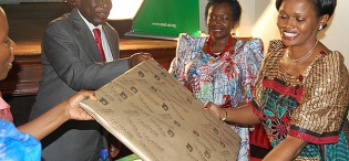 The Nnabagereka (R) receives a gift from The Chairperson Council (2nd L) as Finance Minister-Hon. Maria Kiwanuka applauds during Her Royal Highness' visit on 21st October 2011, Makerere University, Kampala Uganda